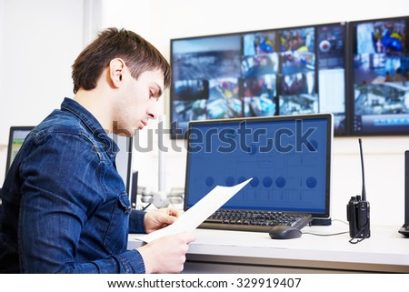 security guard watching video monitoring surveillance security system #329919407