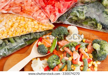 Frozen vegetables on cutting board and plastic bags #330074270