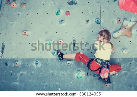 little girl climbing a rock wall indoor #330124055