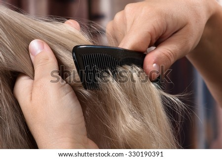 hands of woman combing hair her daughter #330190391