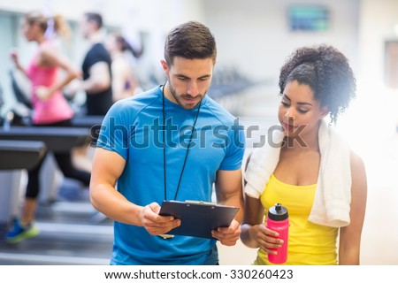 Fit woman talking to her trainer at the gym Royalty-Free Stock Photo #330260423