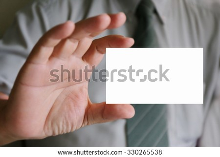 Man's hand showing business card ,Cropped image of the hands of a business man handing over a blank white business card to a woman ready for your contact information #330265538