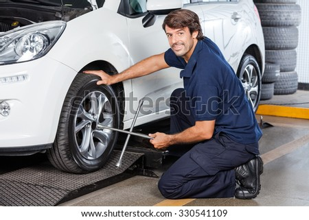 Side view portrait of male mechanic fixing car tire with rim wrench at garage #330541109