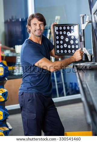 Smiling male mechanic looking away while adjusting wheel aligner on car in garage #330541460