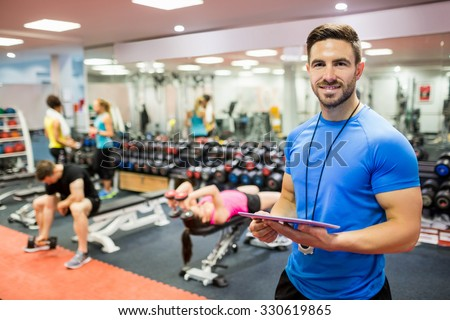 Handsome trainer using tablet in weights room at the gym Royalty-Free Stock Photo #330619865