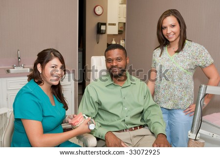 Dental hygienist and dental assistant demonstrating to patient how to clean teeth. #33072925