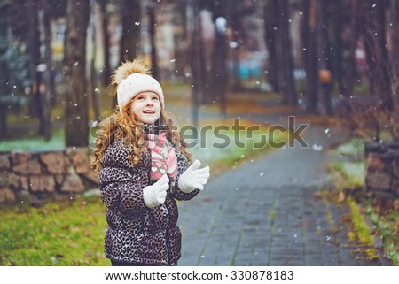 Cute little girl stretches her hand to catch falling snowflakes. Toning instagram filter. #330878183