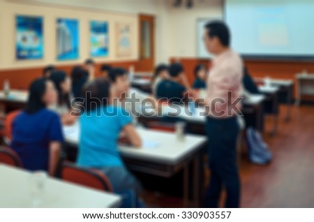 De focused/Blurred image of a teacher giving a lesson in a class.  #330903557