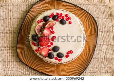 Naked cake with strawberries, figs, grapes and pomegranates on big brown plate. Plate is on beige linen tablecloth. Aerial view. #330969242