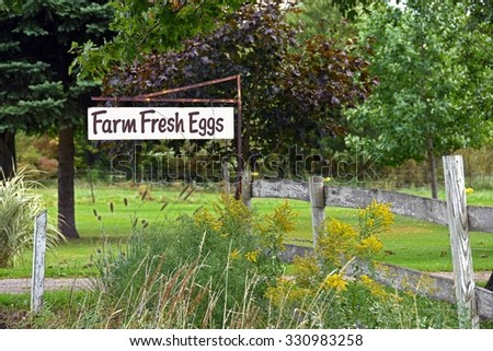 farm fresh egg advertising sign by weathered wooden fence