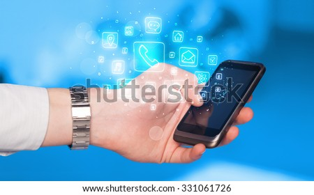 Hand holding smartphone with glowing mobile app icons #331061726