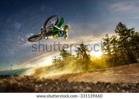 Dirt bike rider is flying high in evening Royalty-Free Stock Photo #331139660