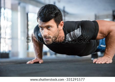 Portrait of a fitness man doing push ups in gym #331291577