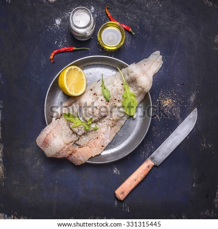 cooking concept raw cod in a pan with herbs and knife on rustic wooden background top view close up