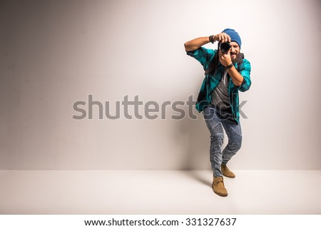 Young cheerful photographer with beard, while working in studio Royalty-Free Stock Photo #331327637