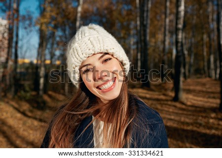 Portrait of a beautiful very cute autumn girl playing in city park. Fall woman portrait of happy lovely and beautiful caucasian young woman in forest in fall colors #331334621