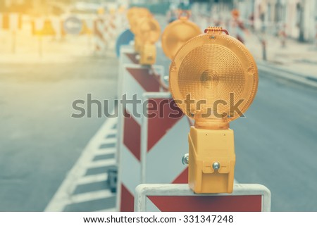 Warning signs for work in progress on road under construction. Vintage and retro style and shallow dof Royalty-Free Stock Photo #331347248