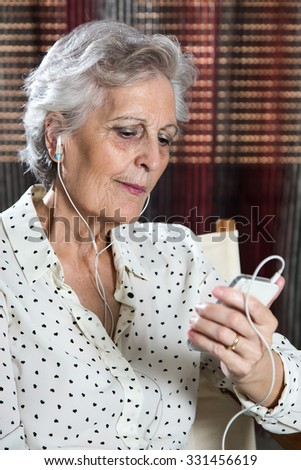 Portrait of a happy senior woman listening to music on mobile #331456619