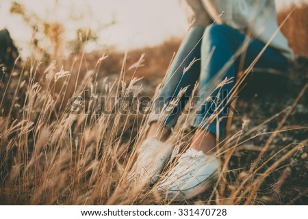 Defocused abstract loneliness concept. Cropped feet of lonely young woman sitting on stone. Solitude Royalty-Free Stock Photo #331470728