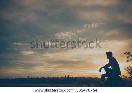 Silhouette of young man sitting on sunset or sunrise. Confident teenage boy thinking on cliff stone. Hope. Sadness. Freedom.