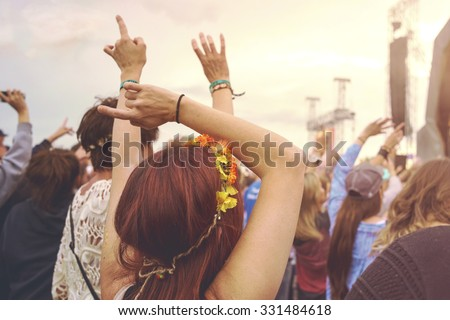 Crowd at an outdoor music festival with outstretched arms Royalty-Free Stock Photo #331484618