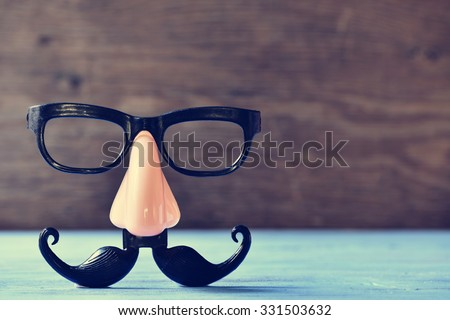 a fake mustache, nose and eyeglasses on a rustic blue wooden surface Royalty-Free Stock Photo #331503632