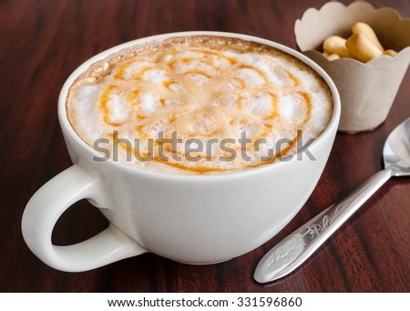 Hot coffee cup with white cream and caramel on the table. #331596860