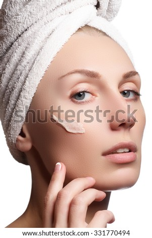 Beautiful face of young woman with cosmetic cream on a cheek. Skin care concept. Closeup portrait isolated on white. Close-up young beautiful face of girl applying moisturize cream #331770494