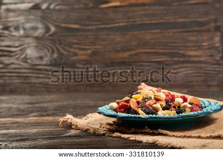Dried fruits. Hazelnuts, almonds, cashews, apricots, cherries, walnuts, raisins. Background - Turkish plate and burlap. Vintage. #331810139