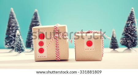 Little handmade gift boxes in a snow covered miniature evergreen forest
