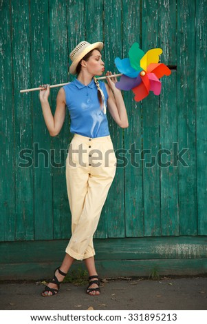 Young happy funny (vintage) dressed woman with colorful weather vane,looking like flower Picture ideal for illustating woman magazines
