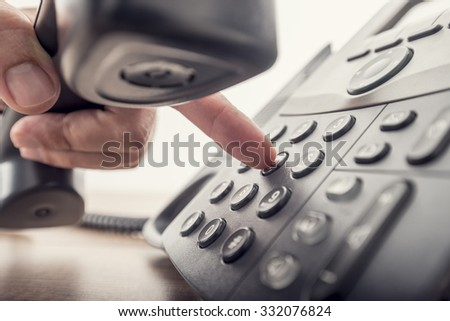 Closeup of male hand holding telephone receiver while dialing a telephone number to make a call using a black landline phone. With retro filter effect. Royalty-Free Stock Photo #332076824