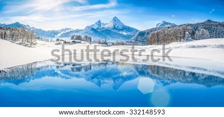 Panoramic view of beautiful white winter wonderland scenery in the Alps with snowy mountain summits reflecting in crystal clear mountain lake on a cold sunny day with blue sky and clouds #332148593