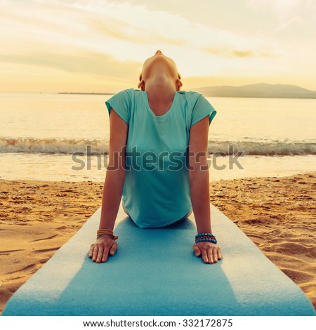 Young woman practicing yoga in upward facing dog pose on beach near the sea on sunset, front view #332172875