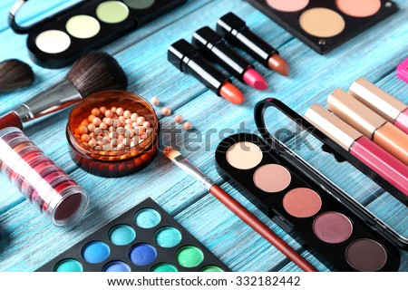 Makeup brush and cosmetics on blue wooden table Royalty-Free Stock Photo #332182442