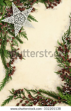 Christmas background border with silver star and ball decorations, fir and cedar cypress leaf sprigs over old parchment paper.   #332201138