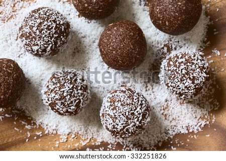 Coconut rum balls being covered with grated coconut on wooden plate, photographed overhead with natural light (Selective Focus, Focus on the top of the balls) Royalty-Free Stock Photo #332251826