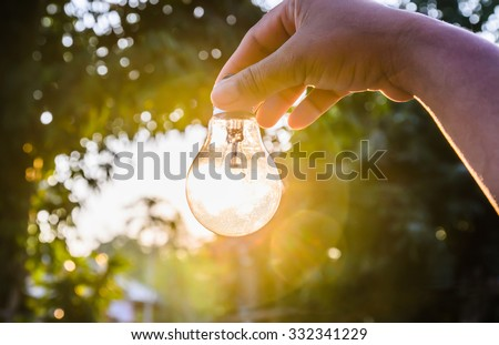and holding a light bulb with sunset power concept #332341229