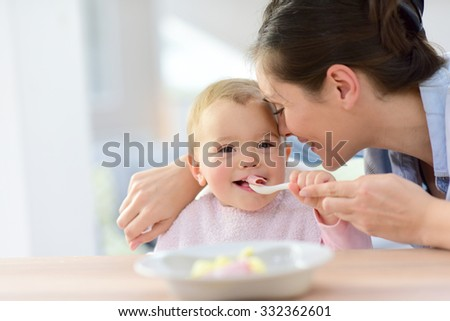 Baby girl eating lunch with help of her mommy #332362601