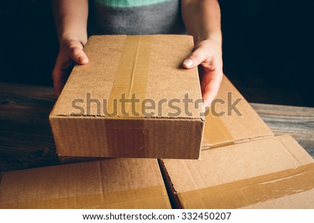 Girl's hands holding the package on the table #332450207