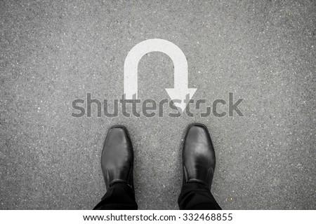 black shoes standing on the asphalt concrete floor in front of u turn symbol #332468855