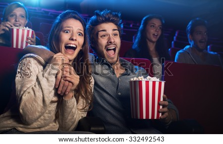 Young scared couple at the cinema watching an horror movie and screaming, she is holding her boyfriend's hand #332492543