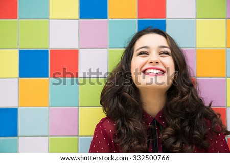 Happy girl laughing against a colorful tiles background. Concept of joy Royalty-Free Stock Photo #332500766