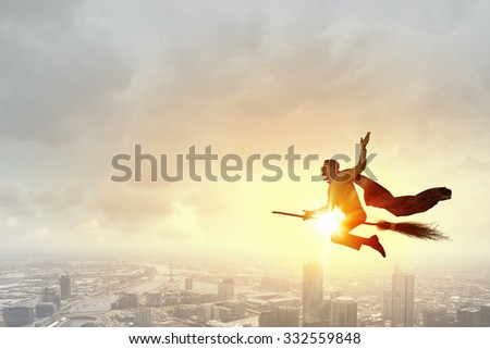 Young businessman flying high above city on broom #332559848
