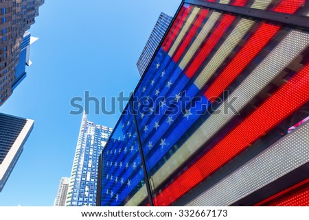 NEW YORK CITY - OCTOBER 10, 2015: neon US flag at Times Square. Times Square is one of the worlds busiest pedestrian intersections and a major center of worlds entertainment industry #332667173