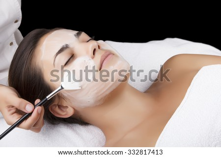 Young pretty woman receiving treatments in beauty salons. Young beautiful dark-haired woman in the office beautician lying on the couch. Facial cleansing foam using. Isolated black. #332817413