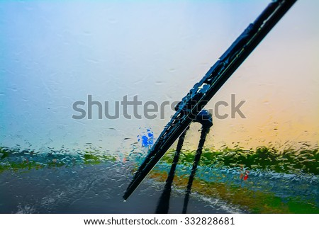 wiper on a wet windshield at sunset Royalty-Free Stock Photo #332828681