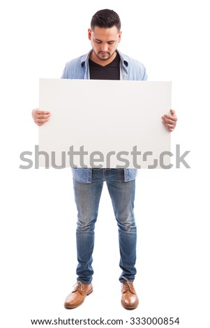 Full length view of a young Hispanic man dressed casually and holding a big sign against a white background #333000854