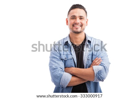 Handsome young Hispanic guy smiling with his arms crossed against a white background #333000917