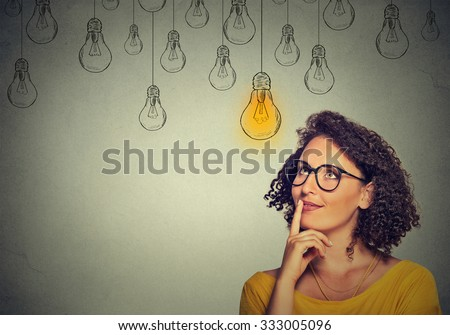 Thinking woman in glasses looking up with light idea bulb above head isolated on gray wall background Royalty-Free Stock Photo #333005096
